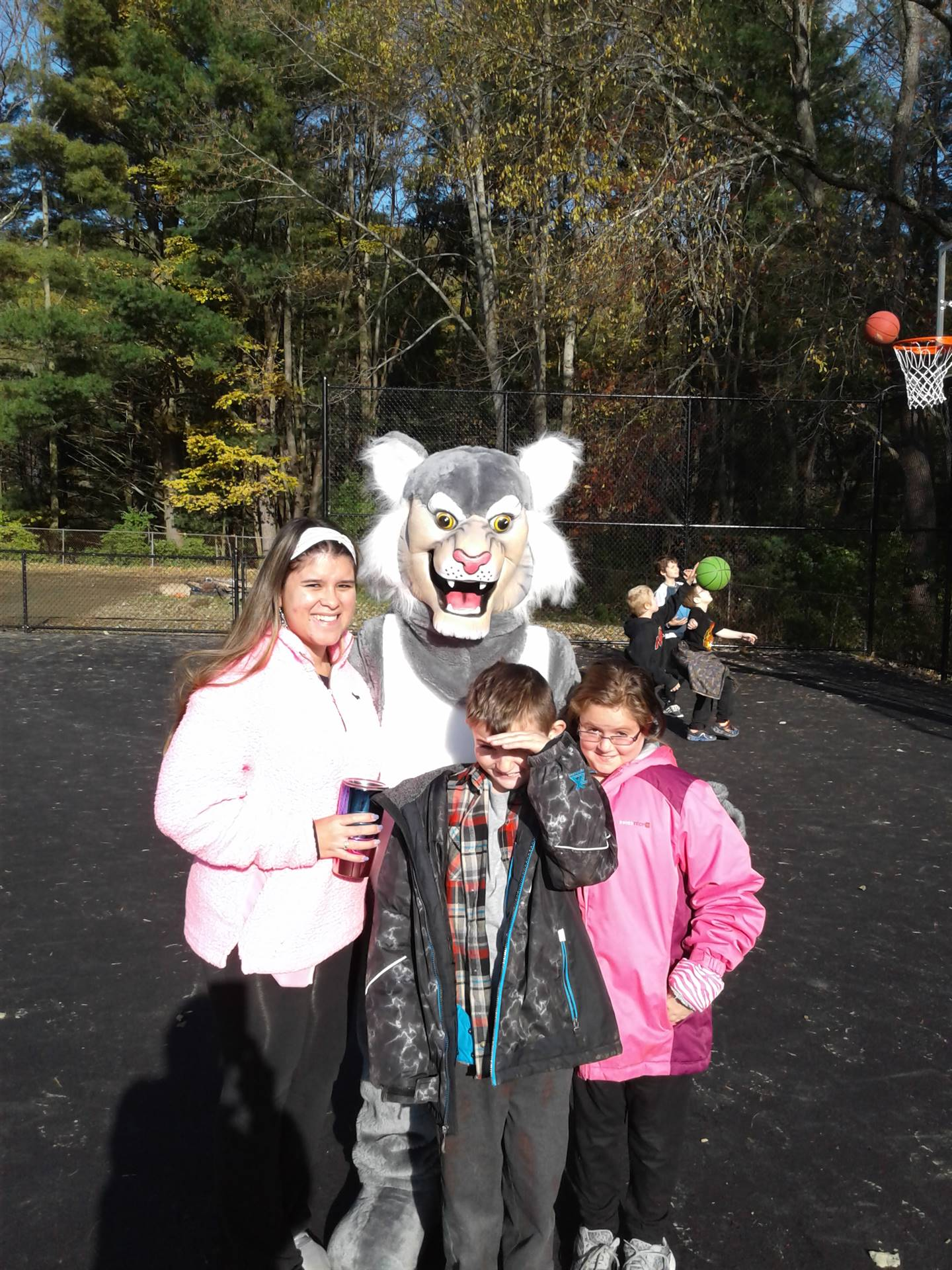 Felix the Bobcat with students on the playground