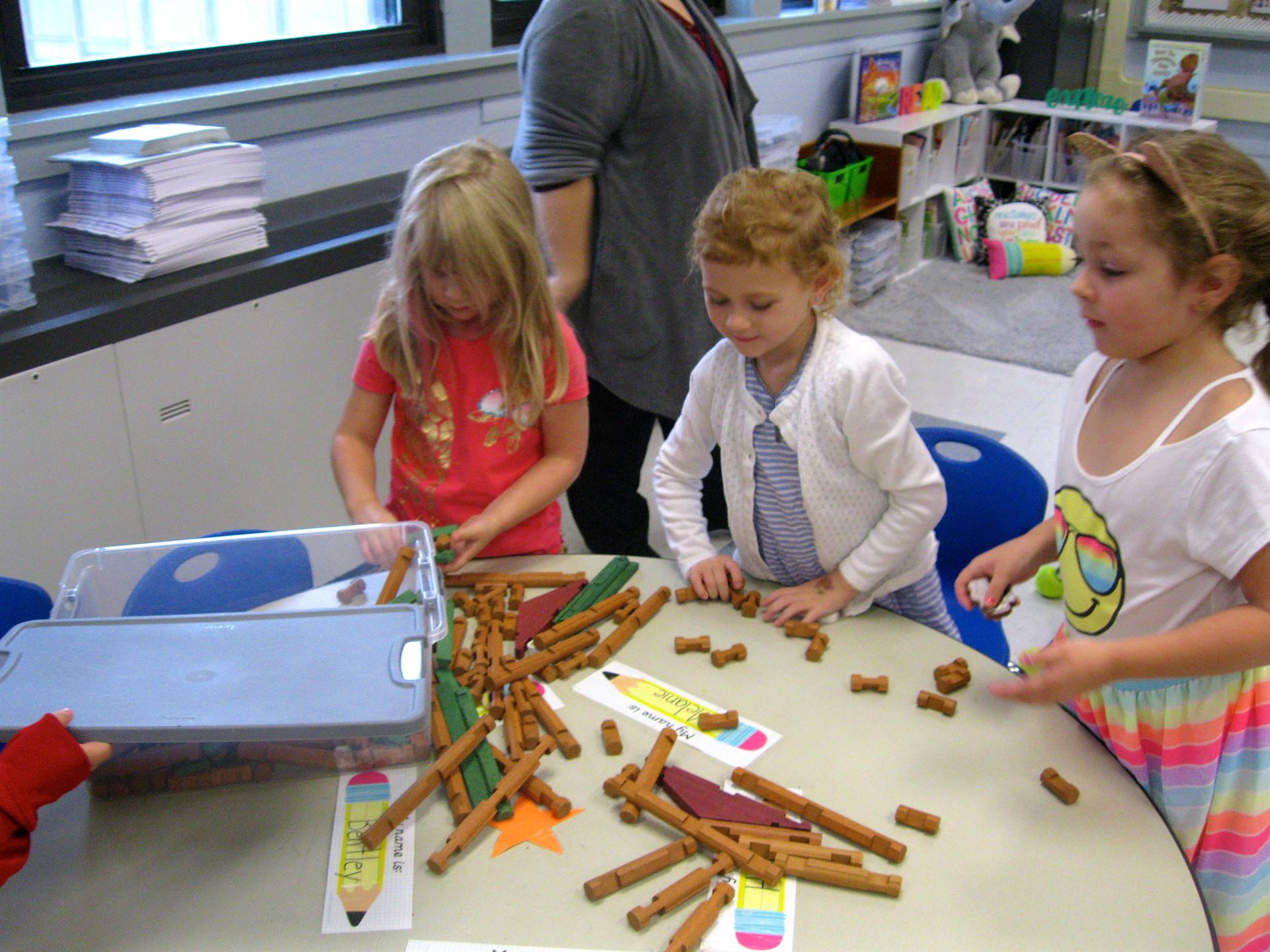 Students use helping hands to pick up.
