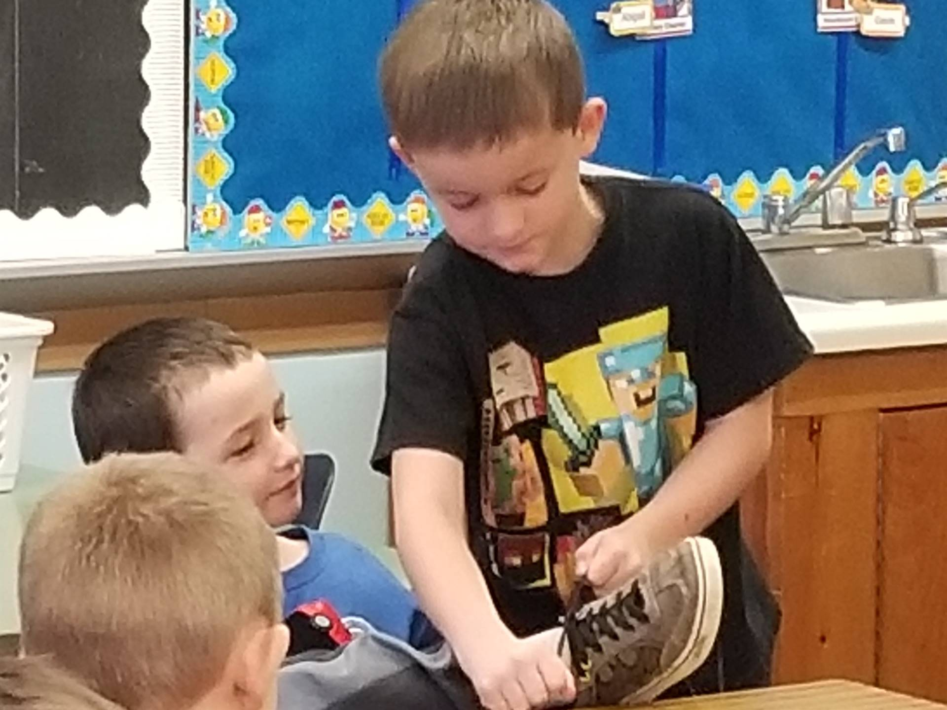 A student uses helping hands to tie another students shoes!