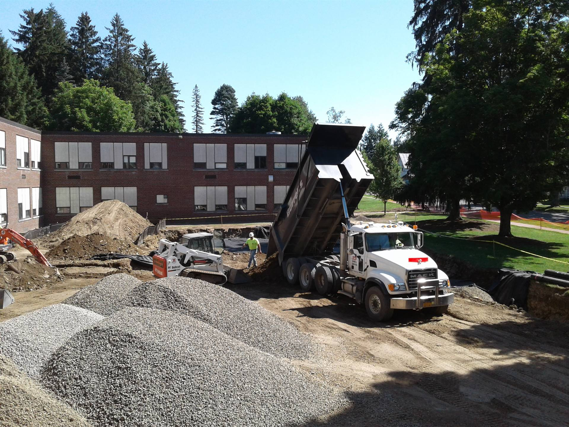 Filling in the big drainage catch basin in front of the High School.