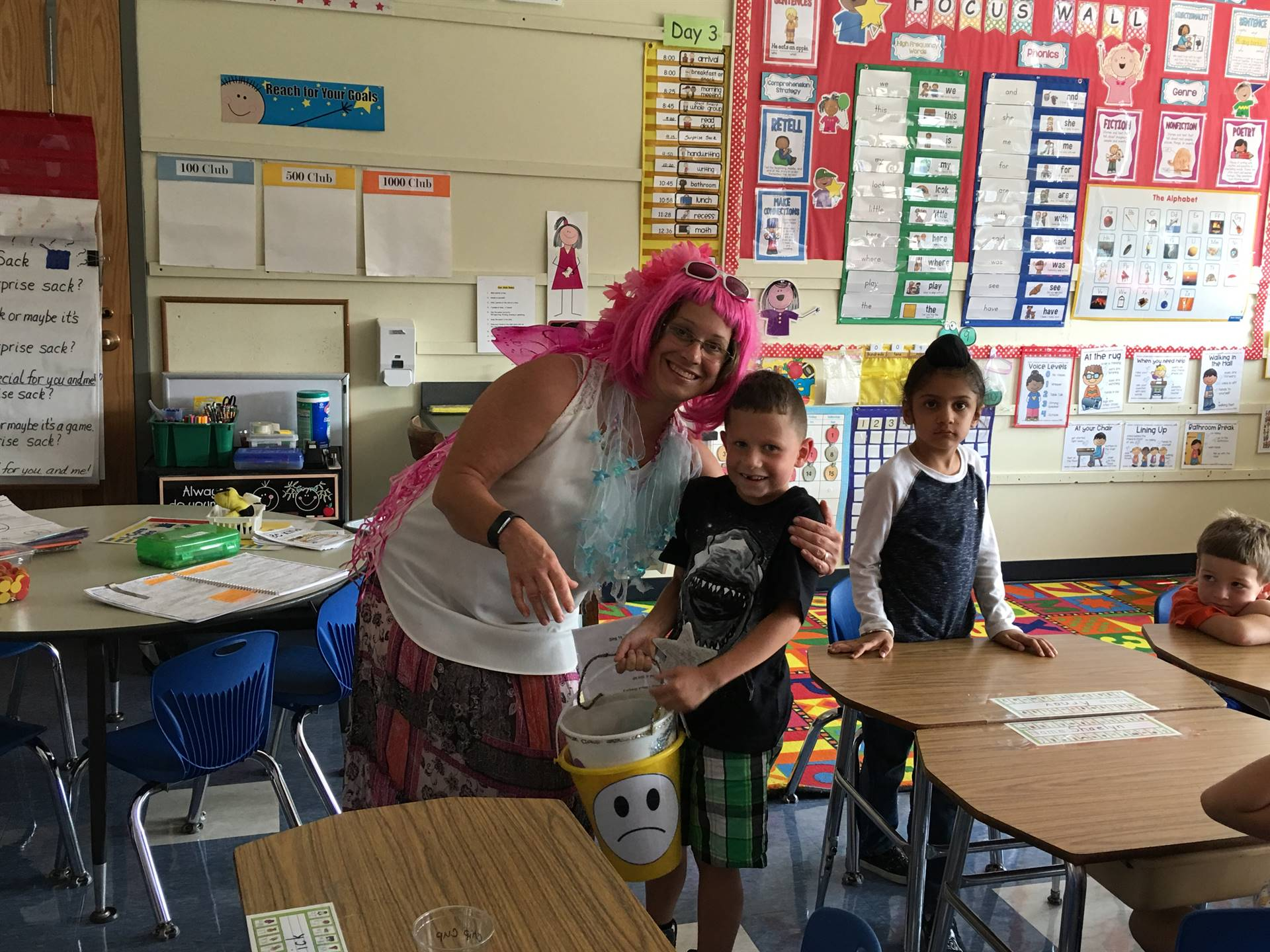 The Bucket Filling Fairy poses with 2 students.