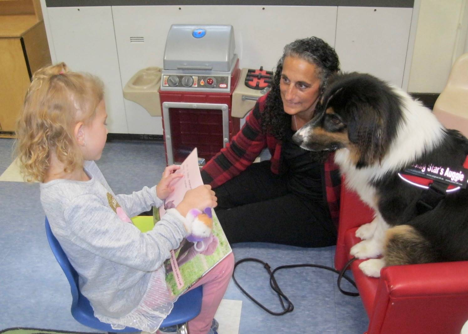 The dog and owner listen to a student reader.