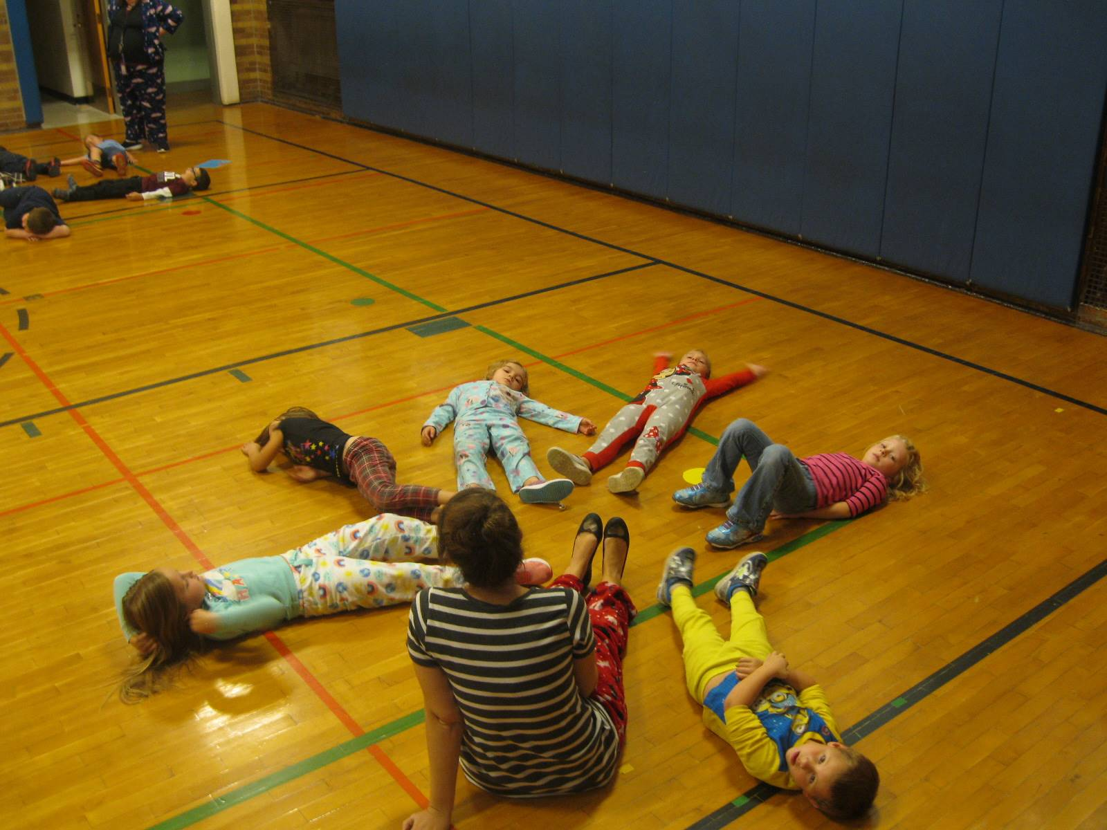 6 students and a teacher relax after a kinder team game.