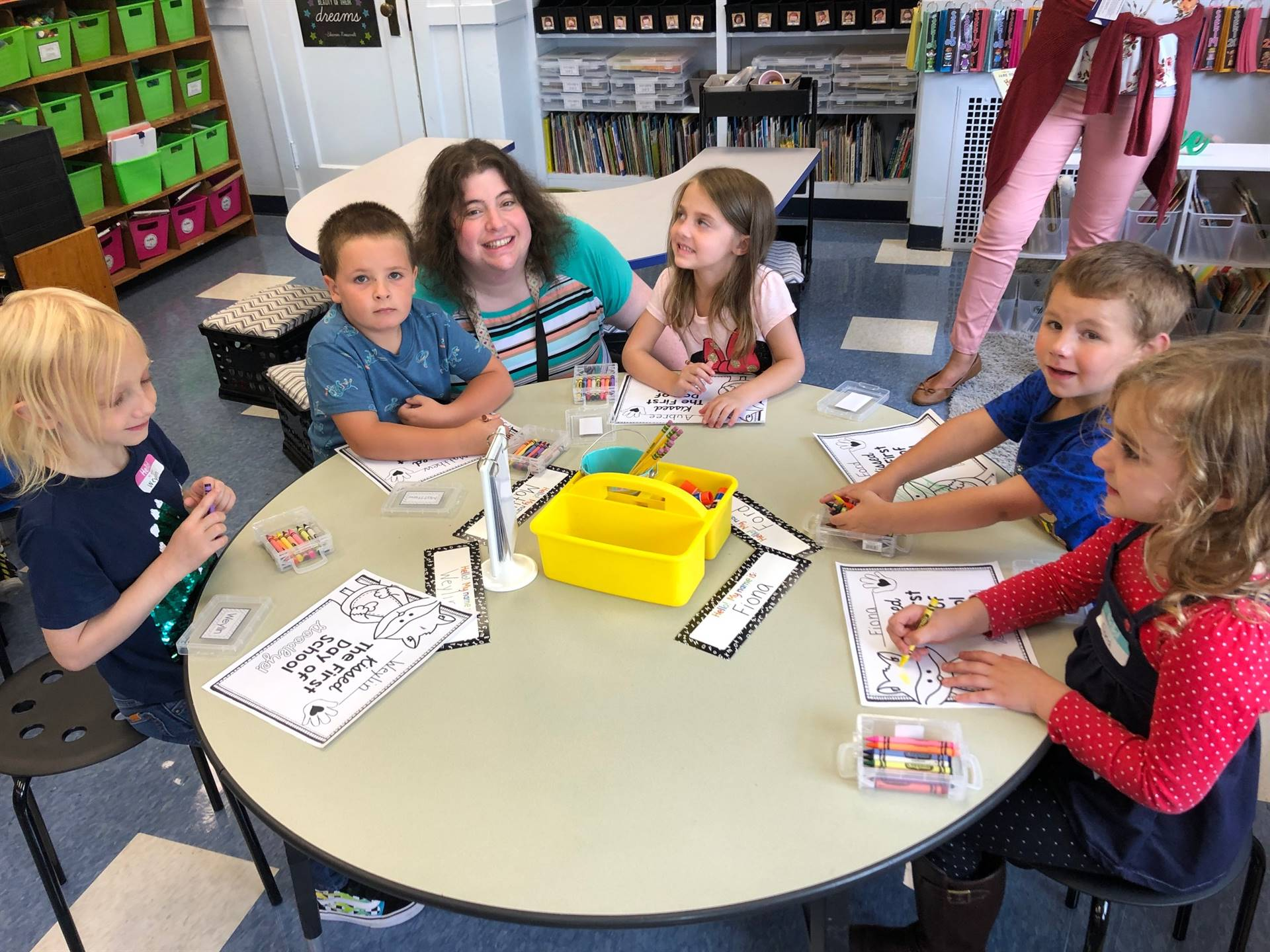 A teacher works with students at a table.