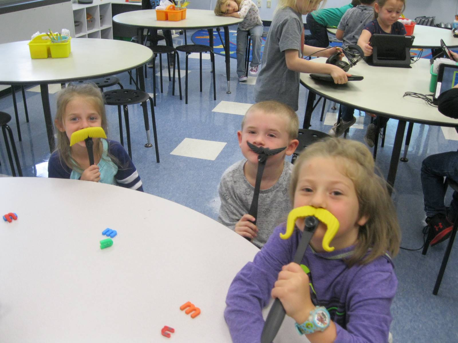 3 students with mustache readers.