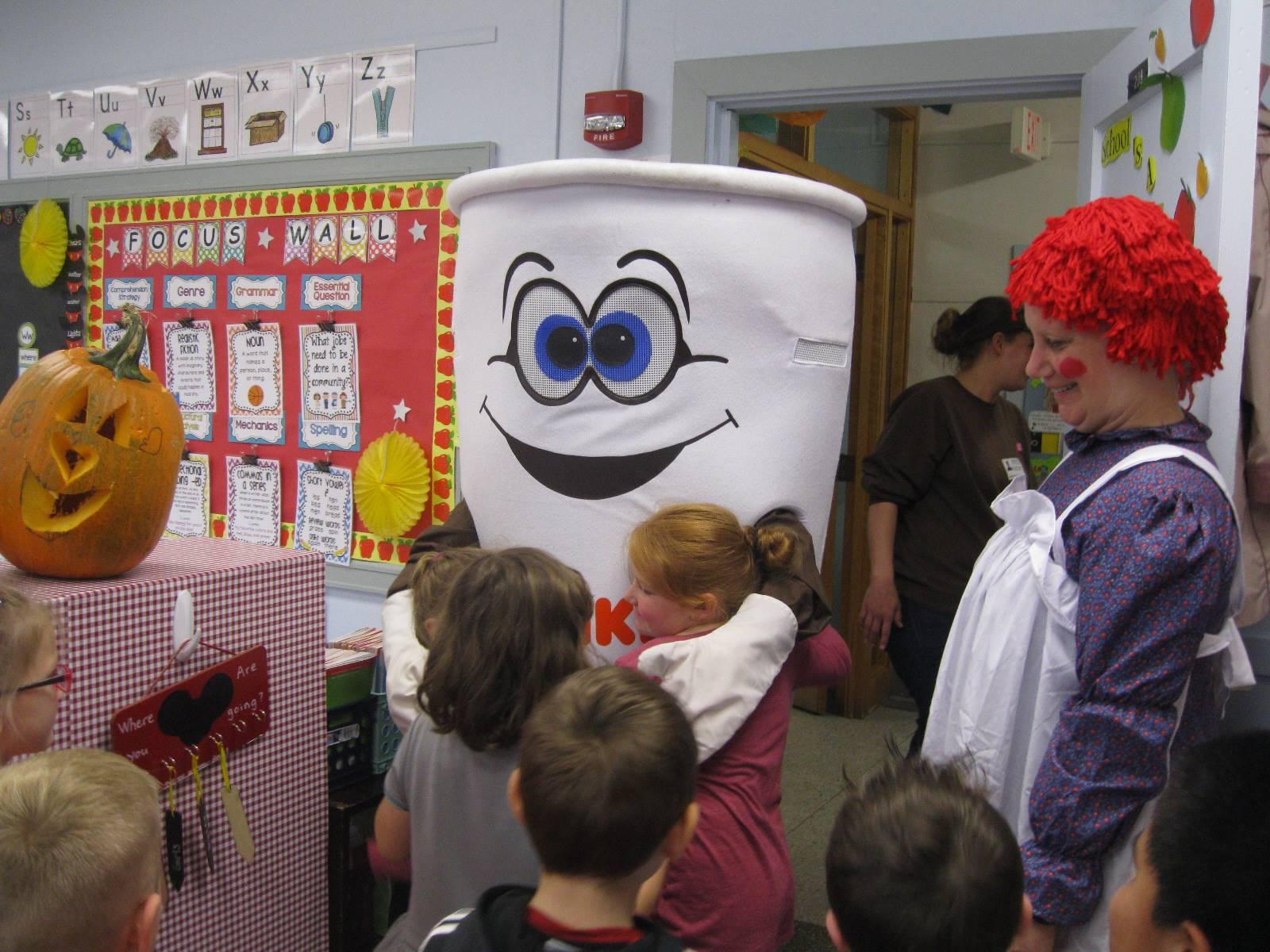 Dunkin Donut man give a student a hug.