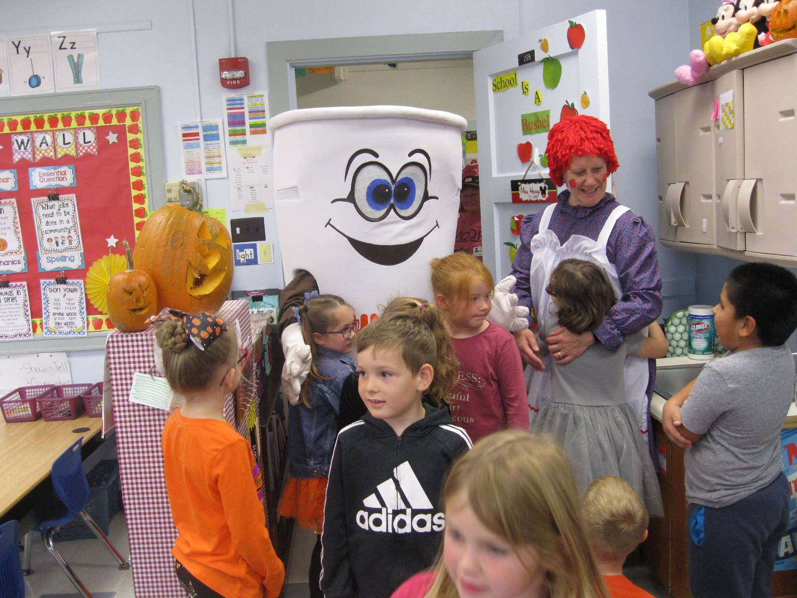 Dunkin Donut man and raggedy ann talk while students watch.