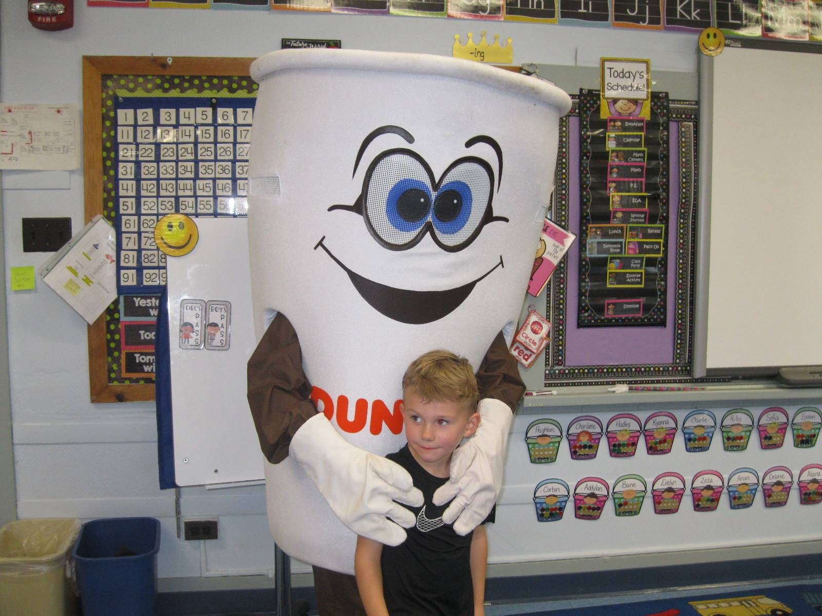 dunkin donut man gives a hug to a student
