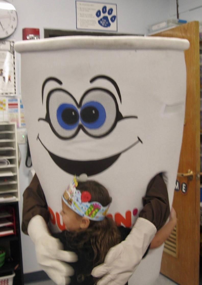 Dunkin donut man gives a birthday girl hugs.