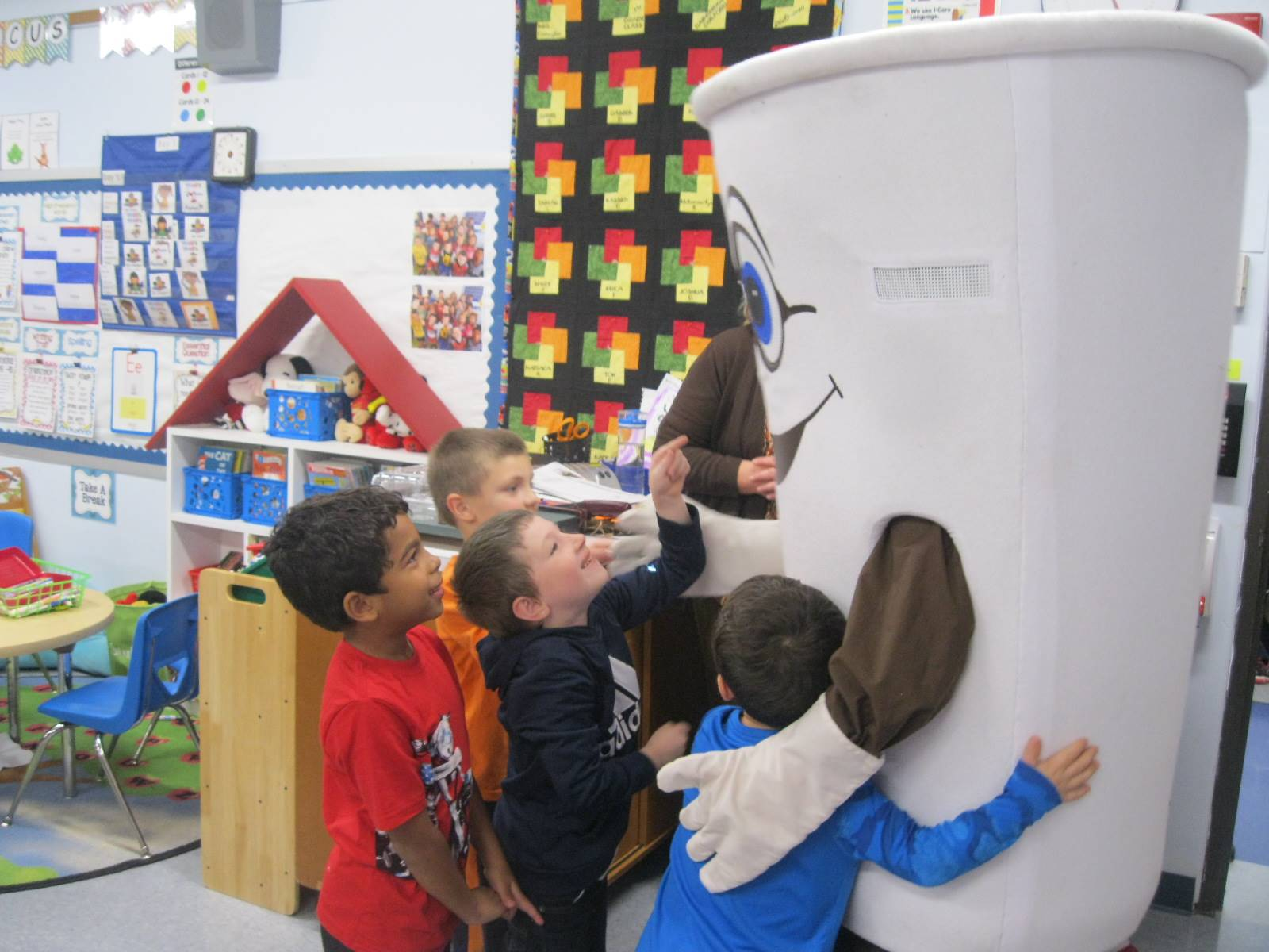 Dunkin donut man gives high 5s to students.