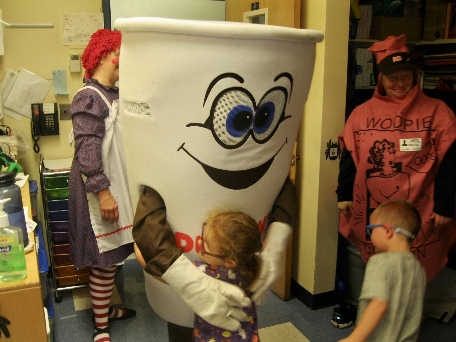 Dunkin donut man gives hugs  to pre k students.