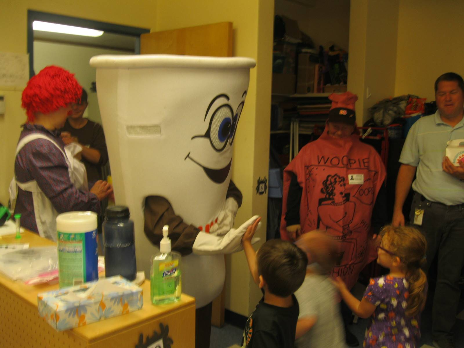 Dunkin donut man gives high 5s to pre k  students.