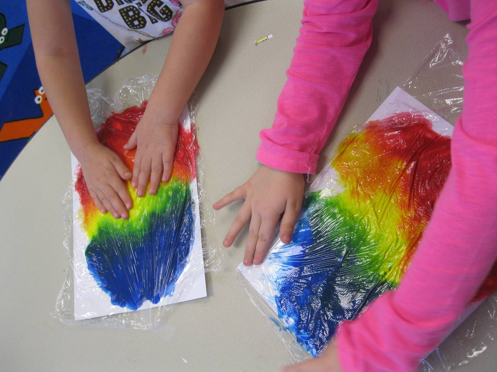 Student hands show how to spread paint.