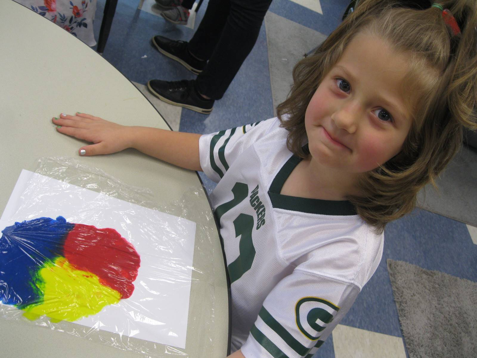 A student shows her art painting.