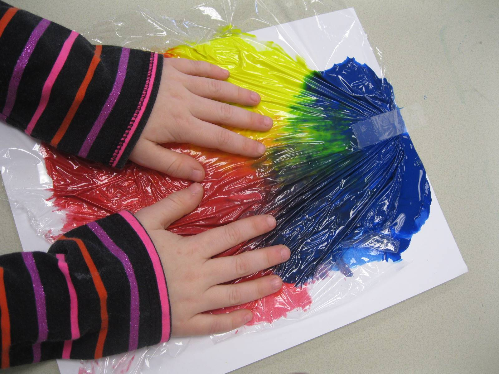 Hands are painting and mixing colors!
