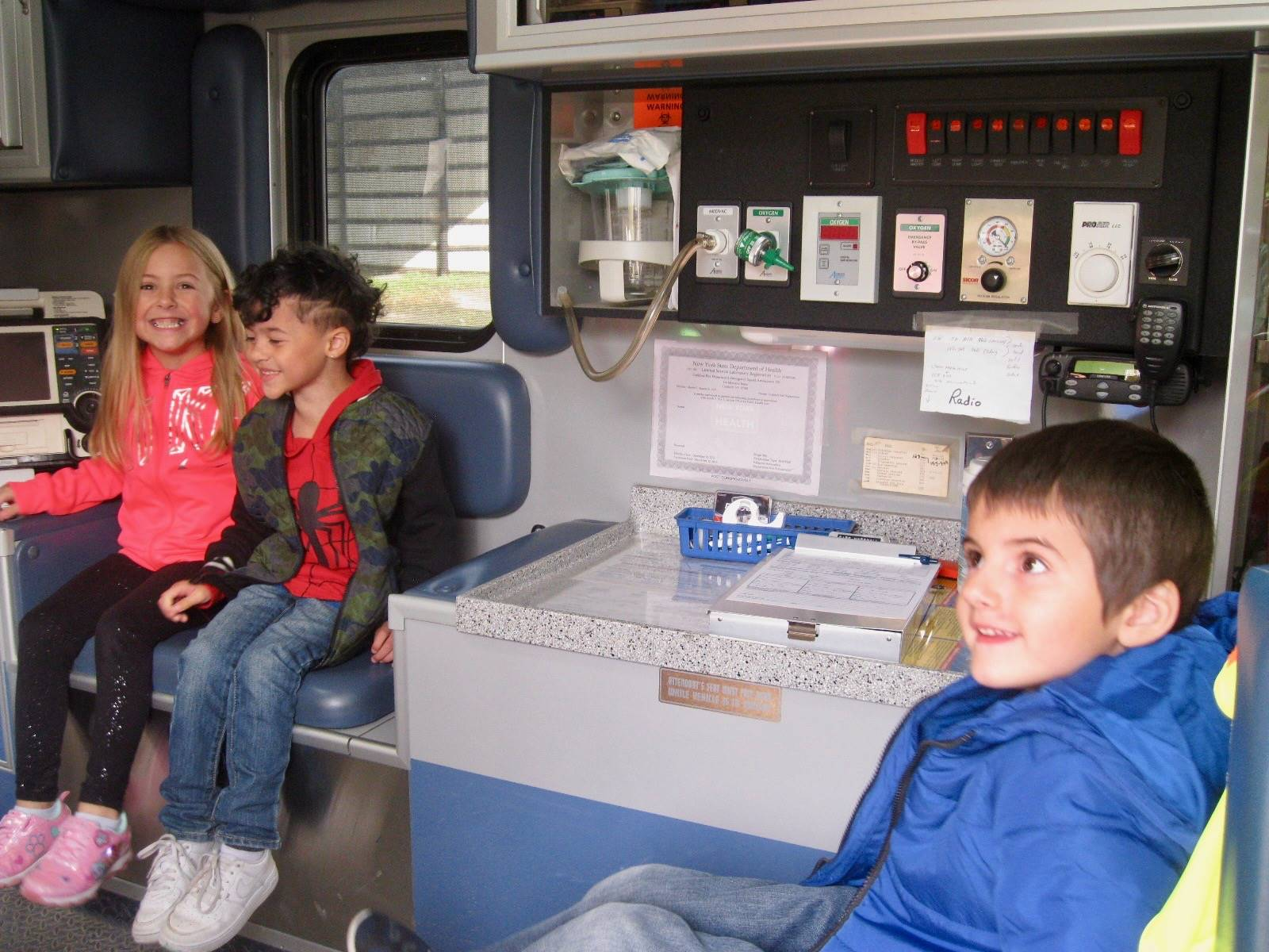 3 students sit in an ambulance