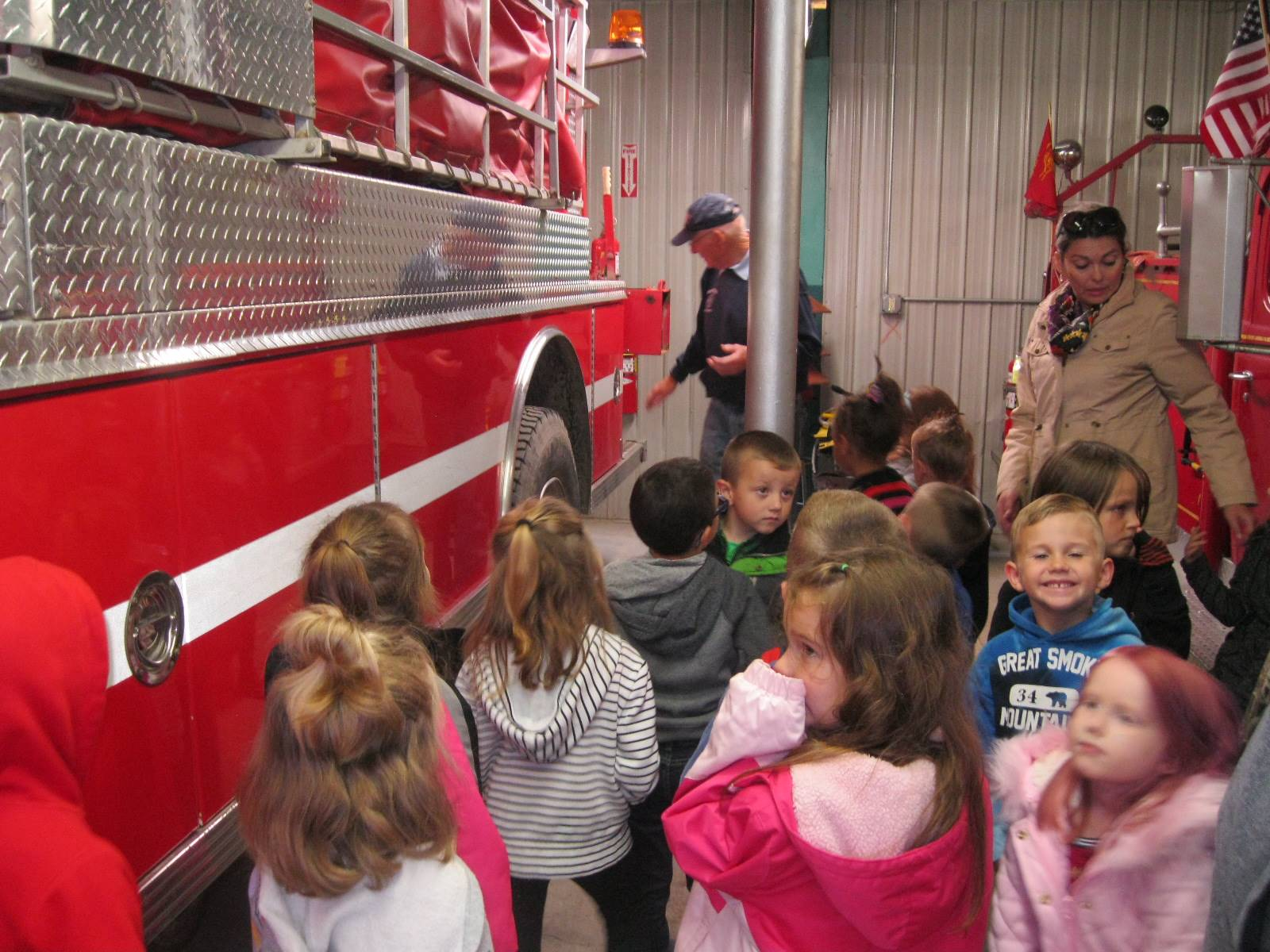 Students look at fire trucks at the fire station.