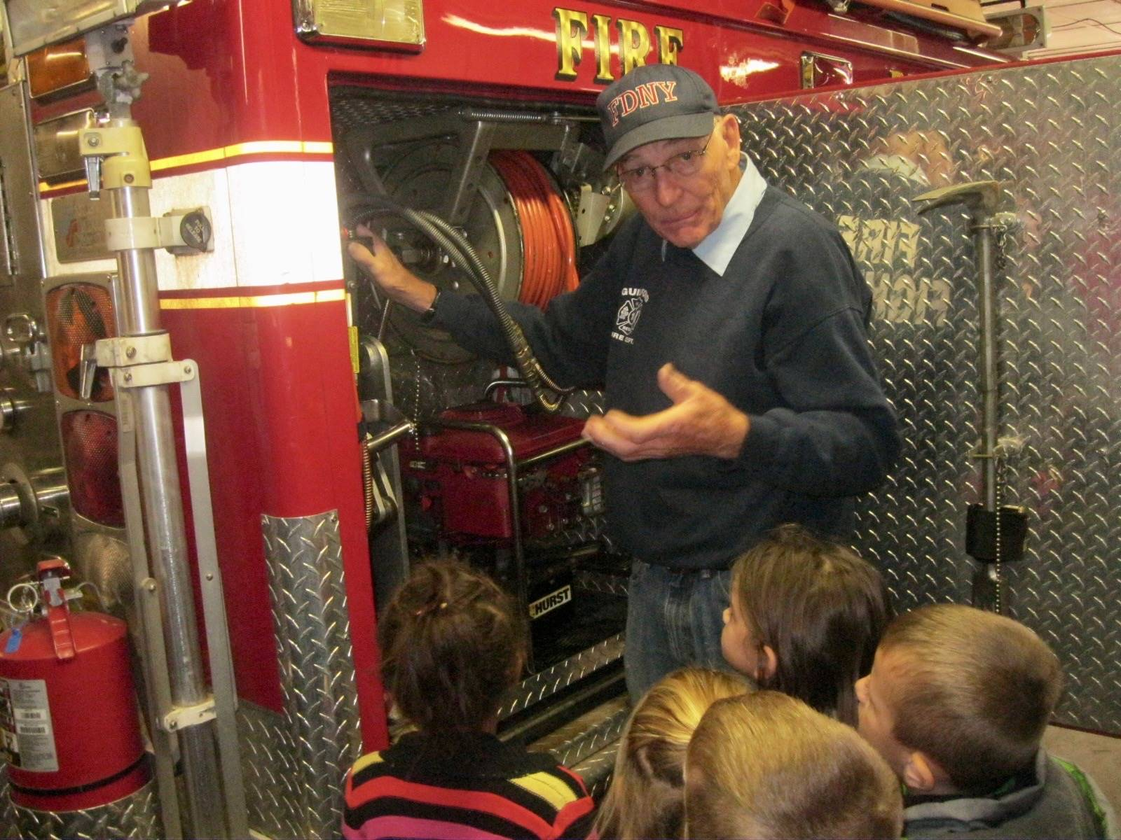 Fireman Bosworth shows equipment to students.