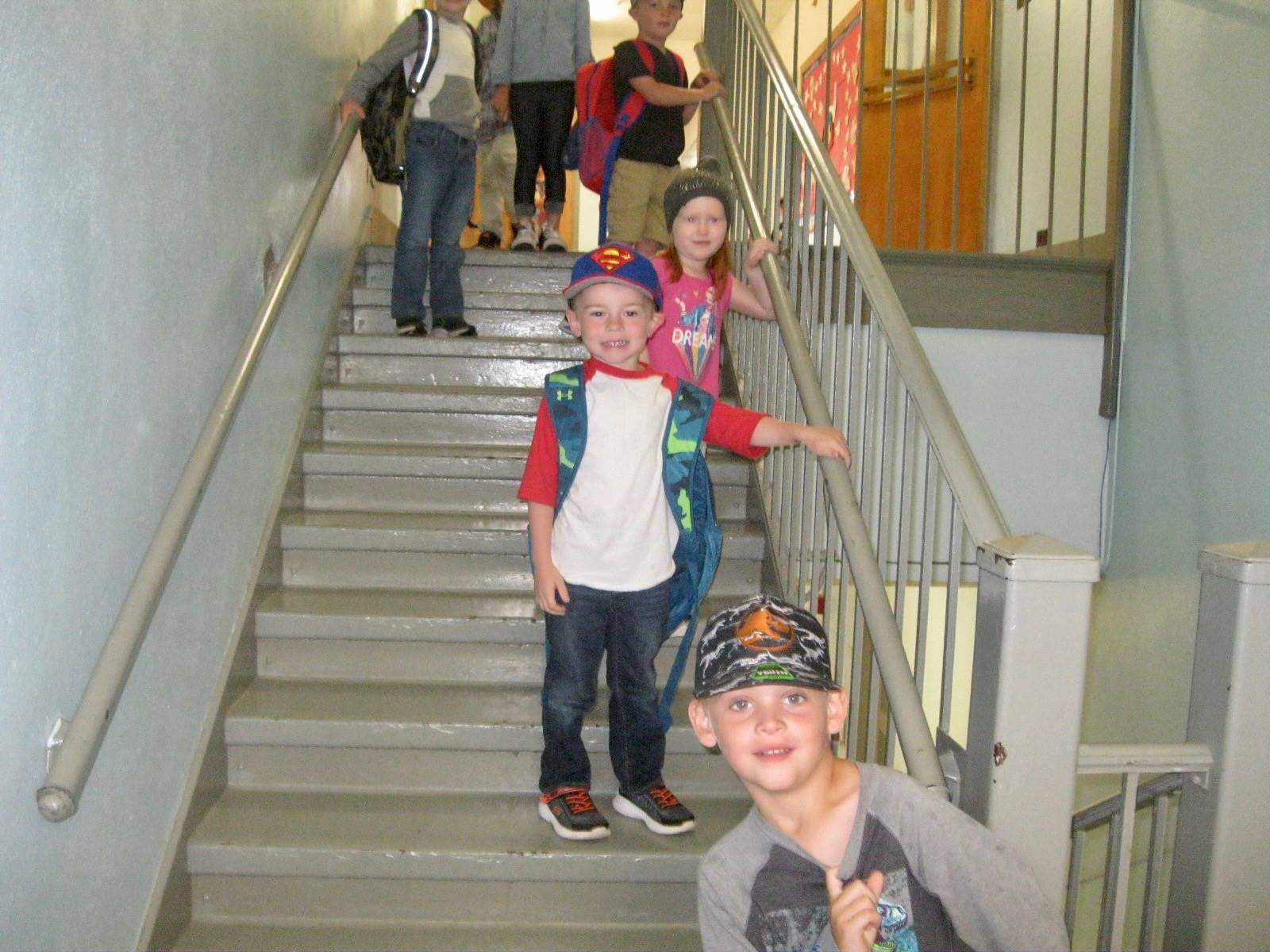 Students on stairs with hats.