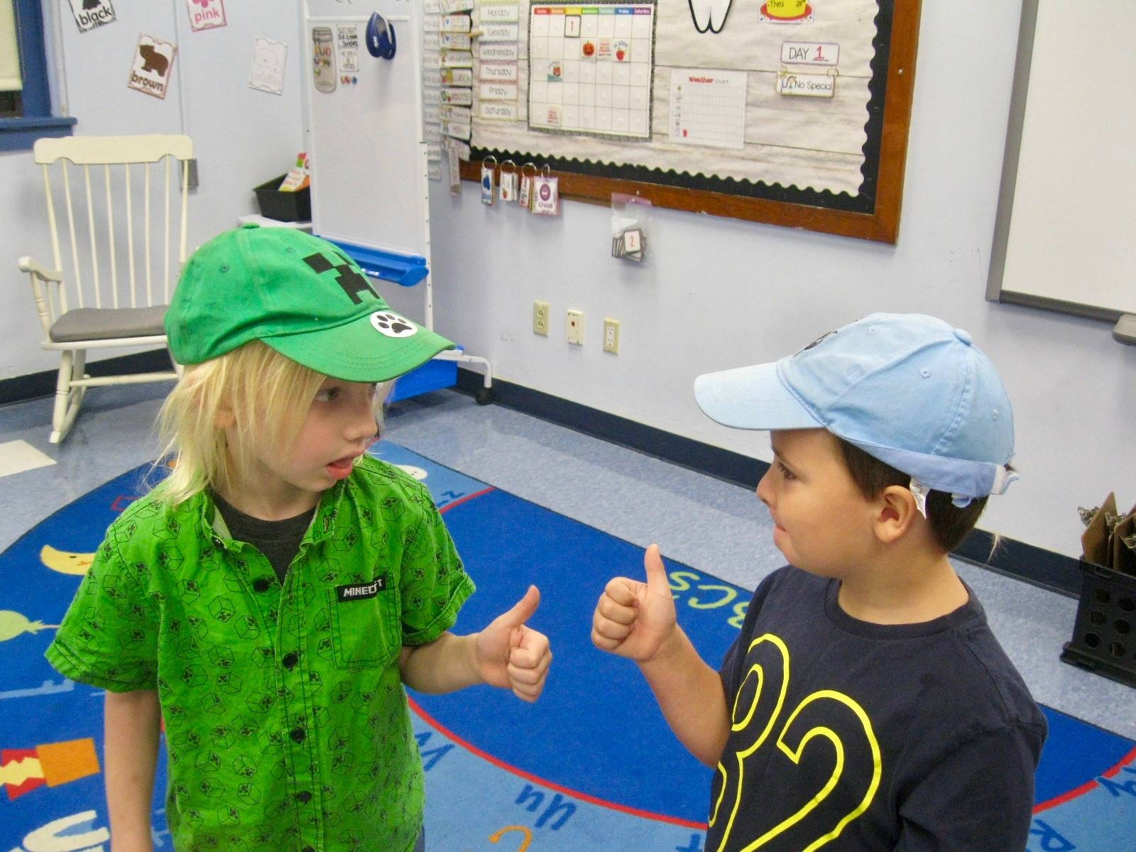 2 students giving each other a thumbs up.