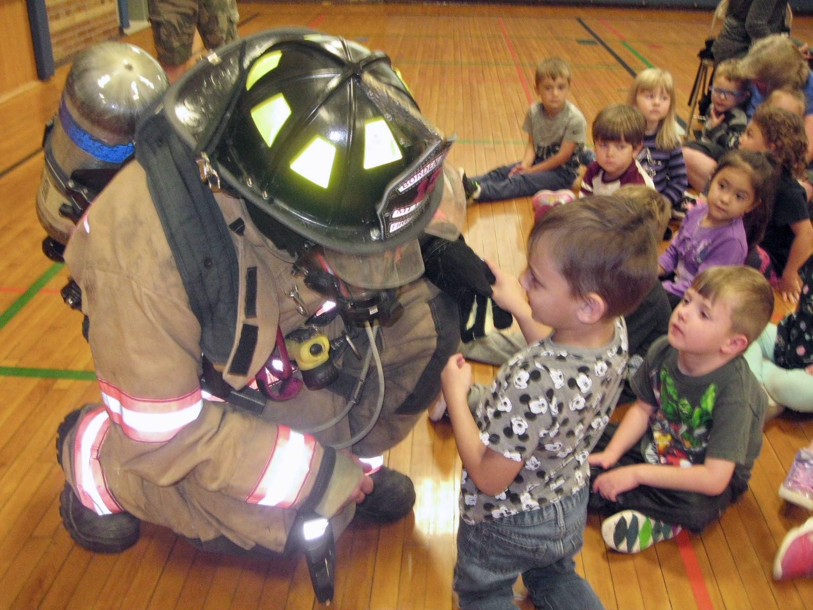 Firefighter talks to a student.