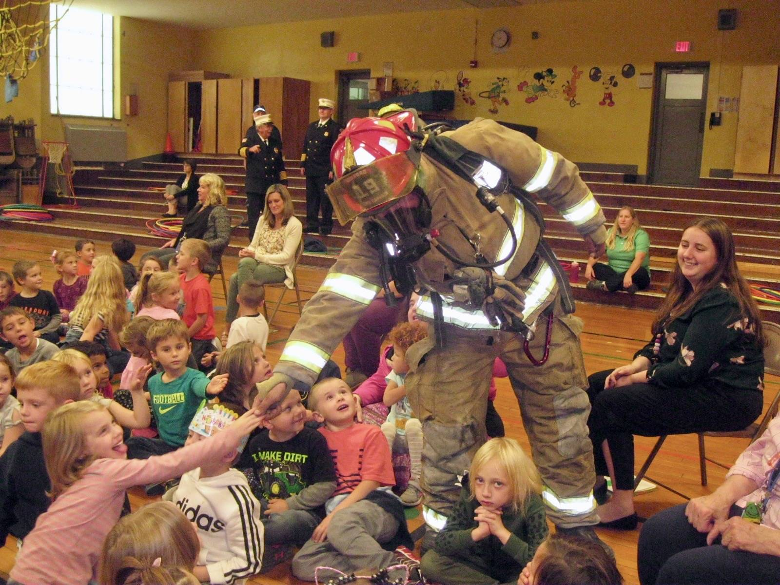 Firefighter gives students high 5's.