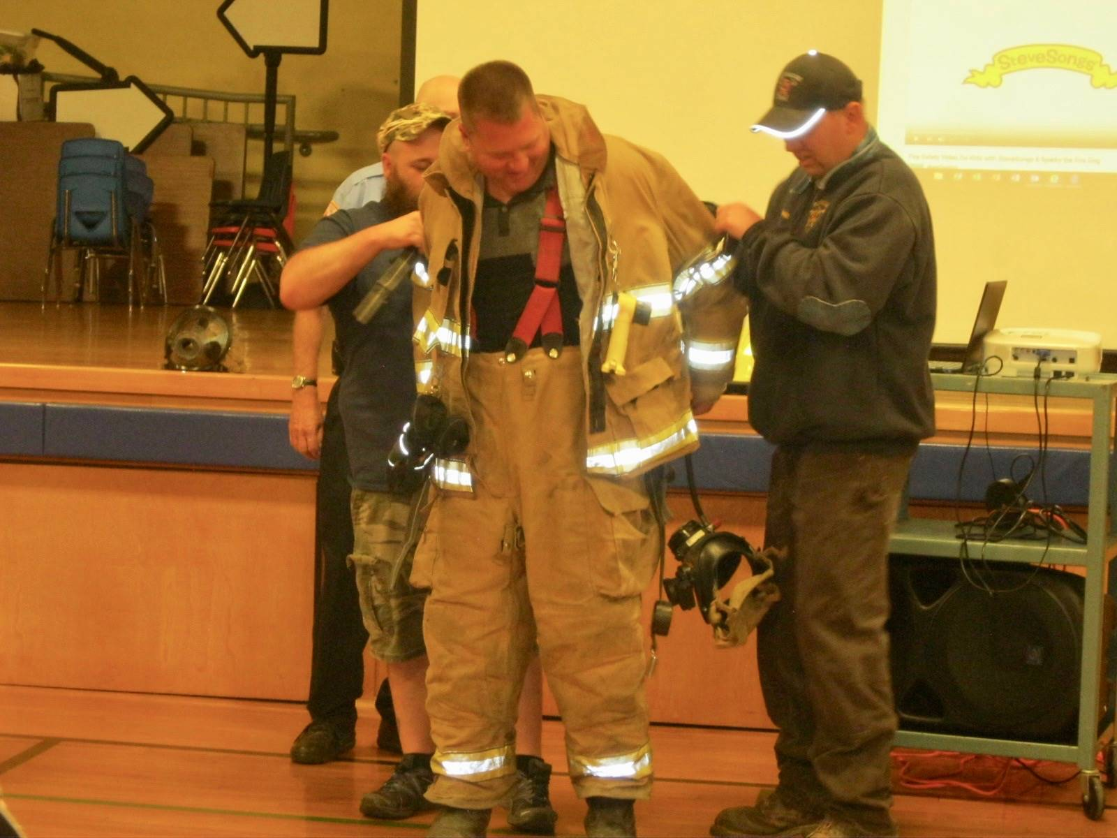 A fire fighter needs help getting their gear off.