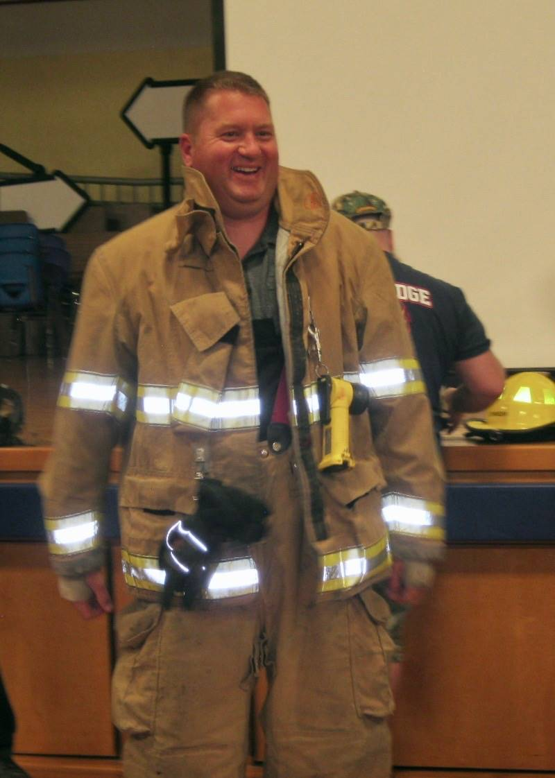 A staff member dressed up in firefighter gear.