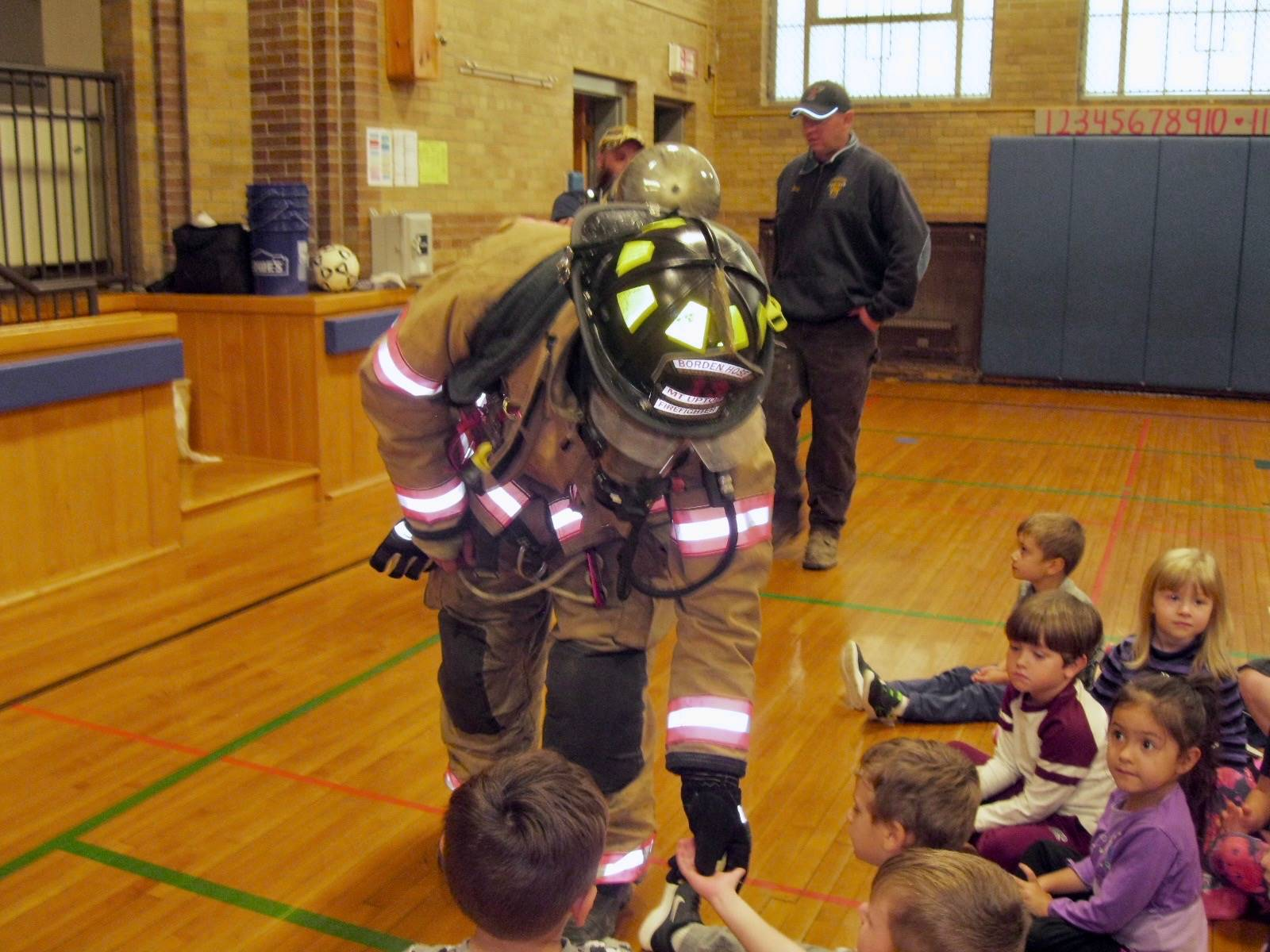 Firefighter shakes students' hands.