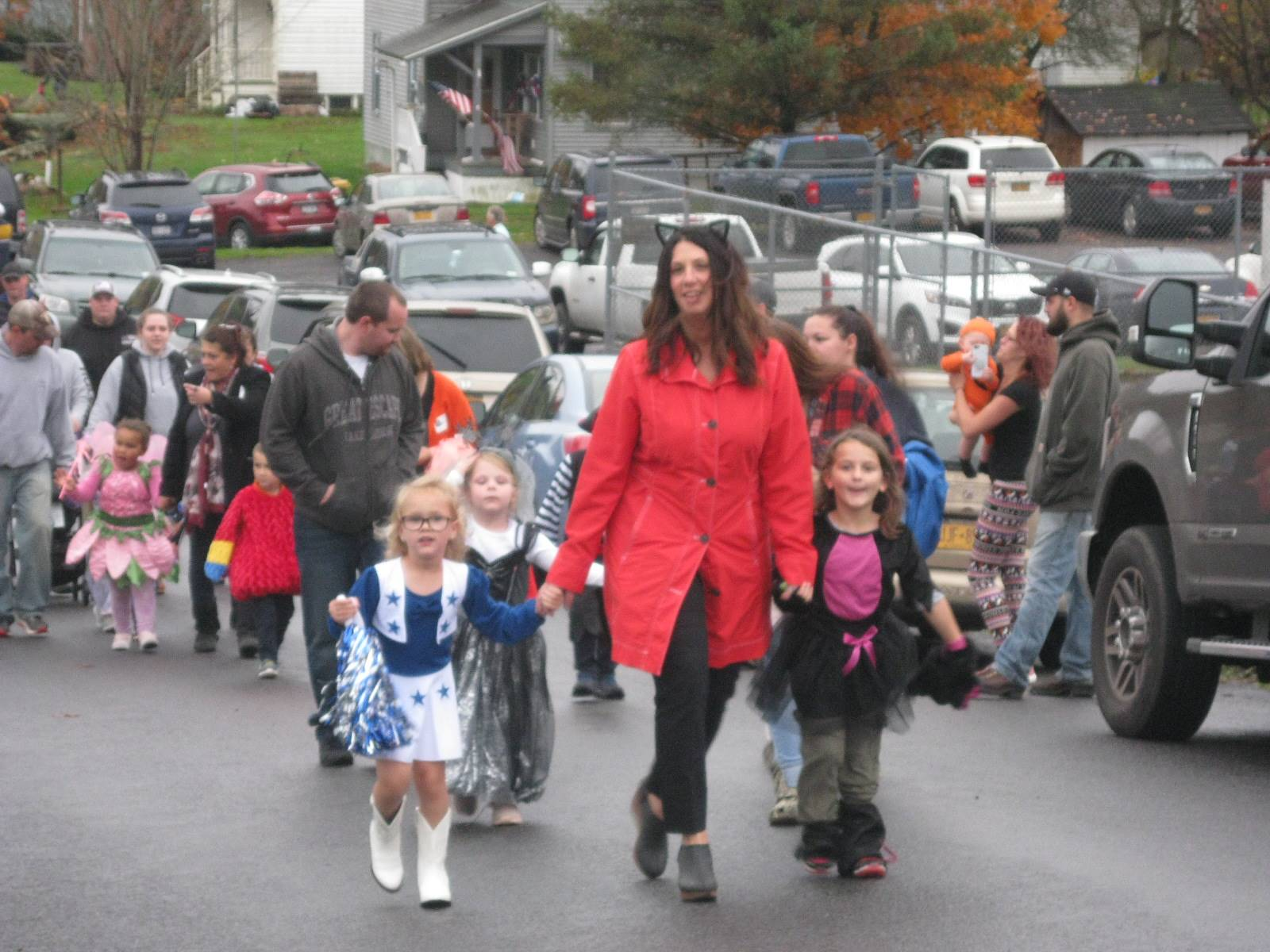 students march in halloween parade with their teacher.