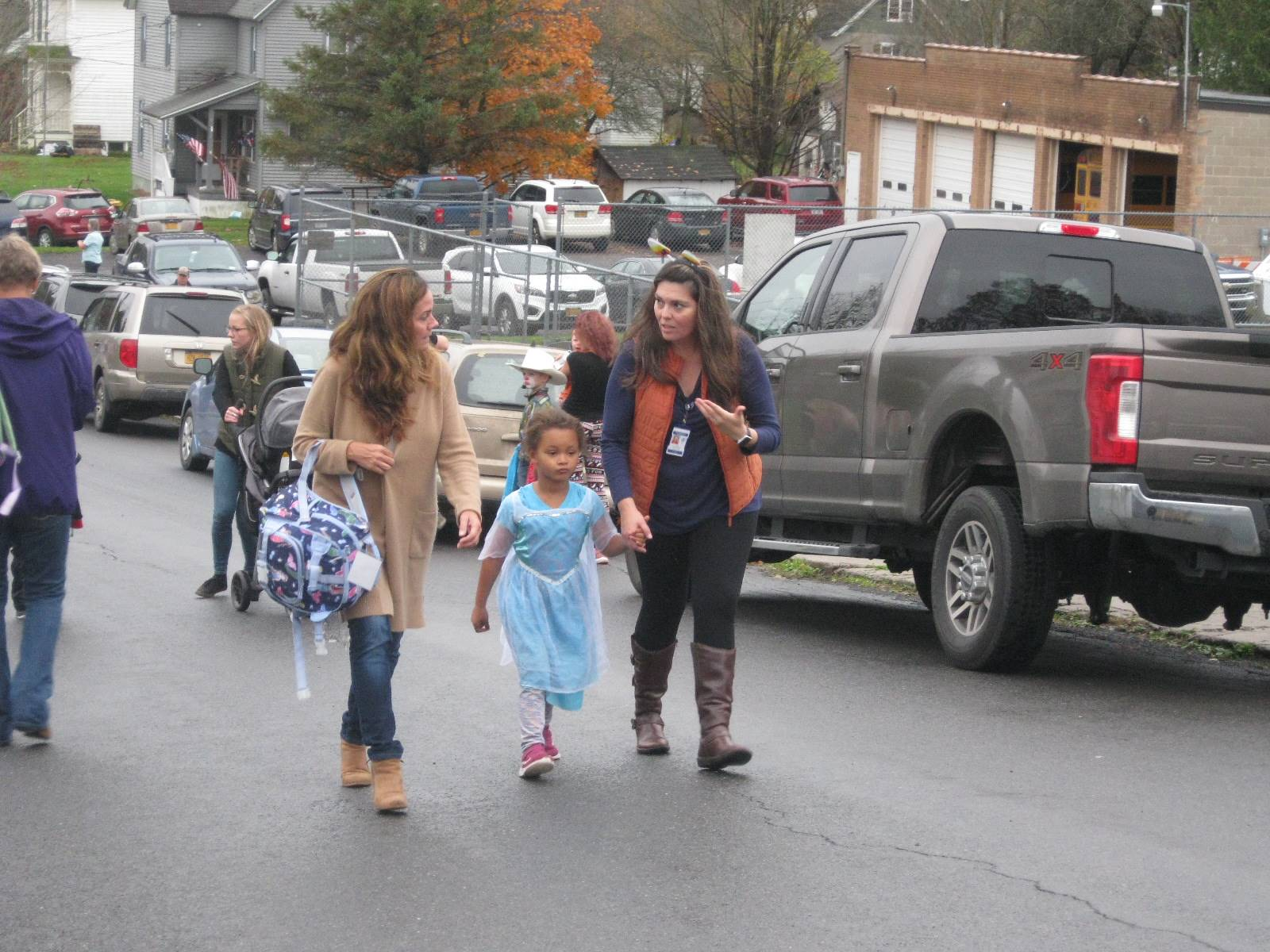 A student marches in between 2 adults in halloween parade