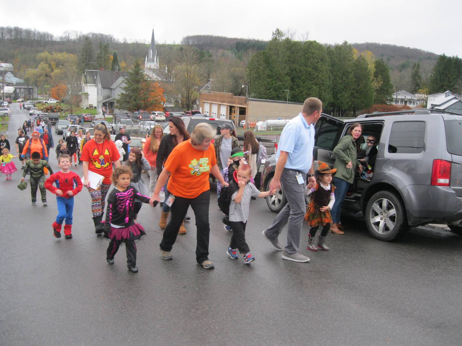 students march in halloween parade with their teachers.