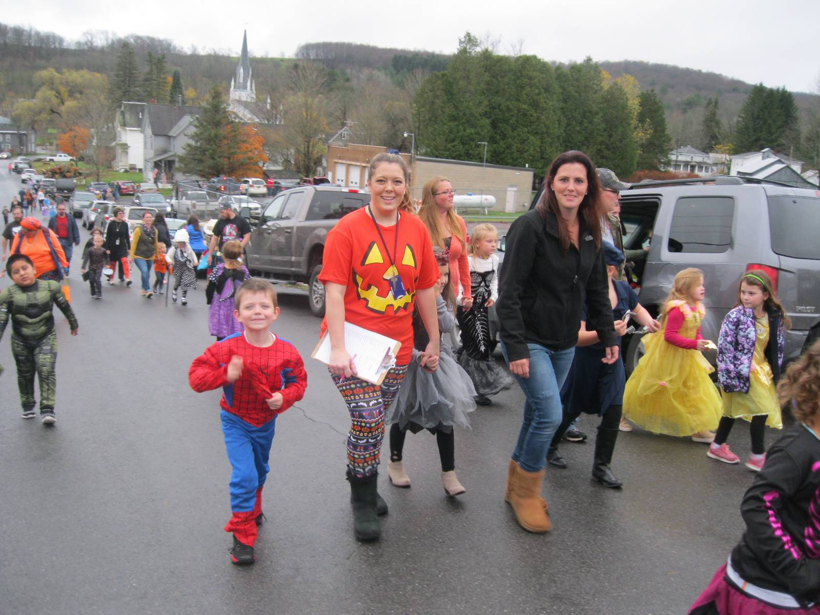 students march in halloween parade with their parents.