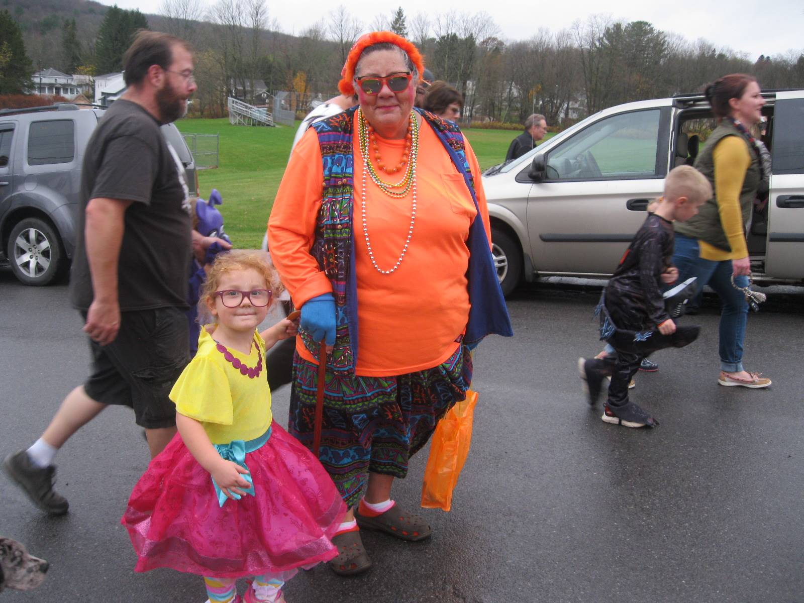 students march in halloween parade with their grandmothers.