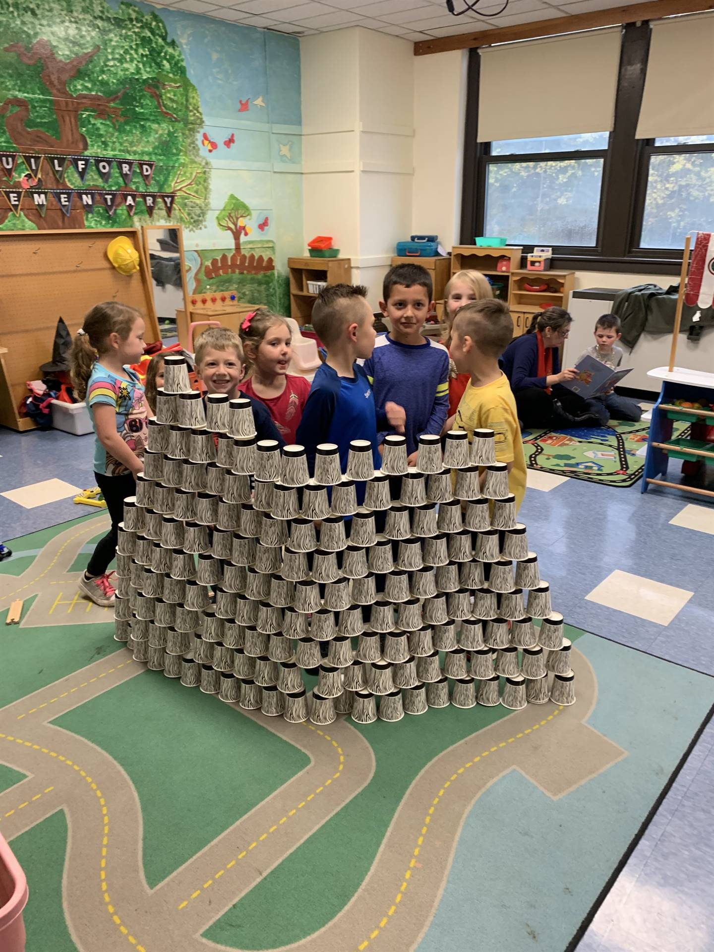 Students build a wall out of cups.
