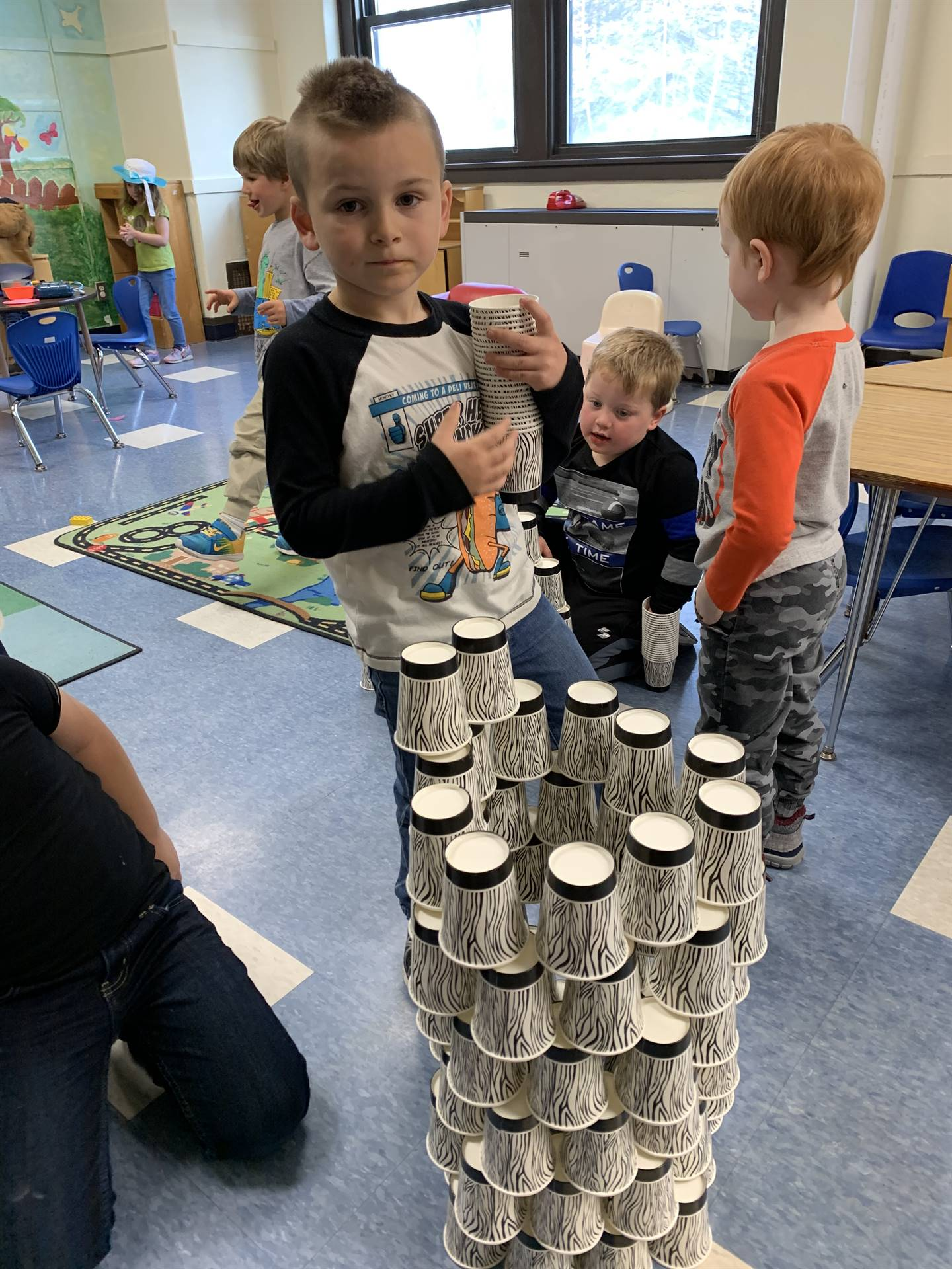 A student stands with his cup tower.