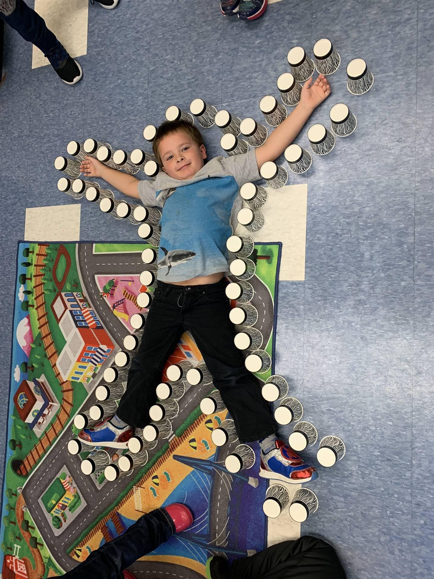 A student lays on floor outlined by cups.
