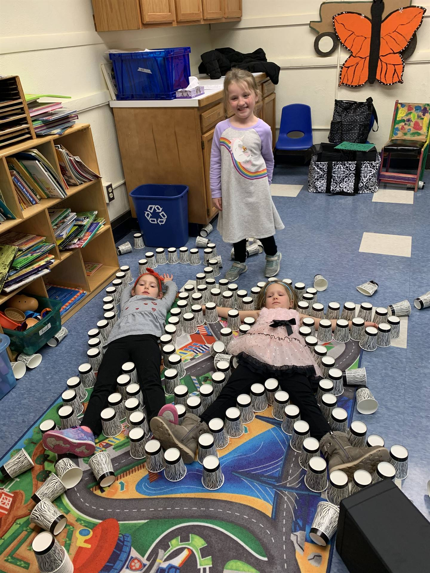 2 students lay on floor outlined by cups.