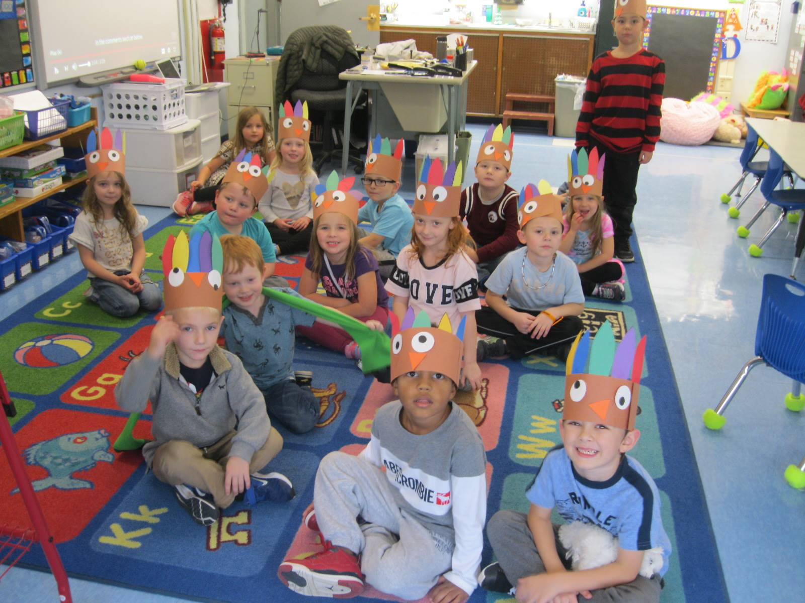 A class shows off their paper turkey hats.