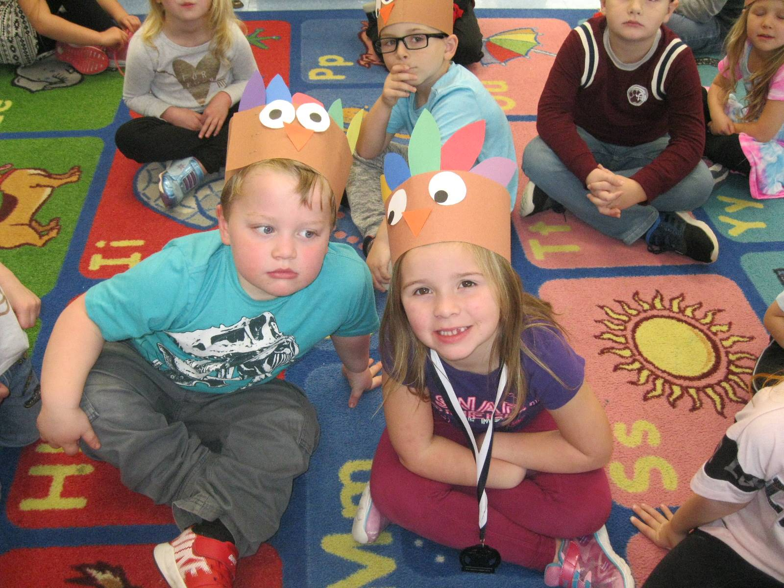 2 students with paper turkey hats.