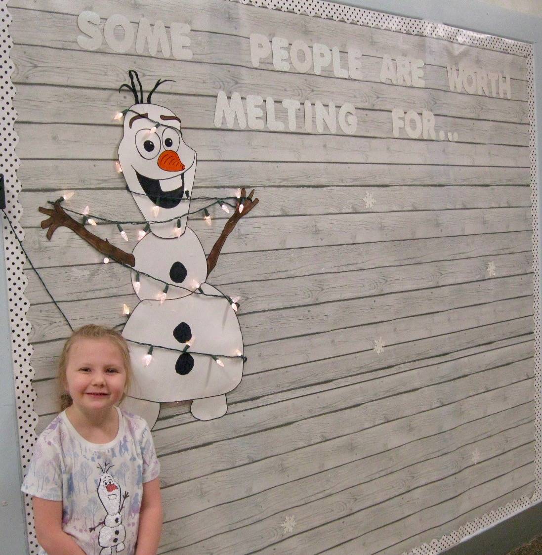 A child with olaf on shirt standing next to Olaf bulletin board.