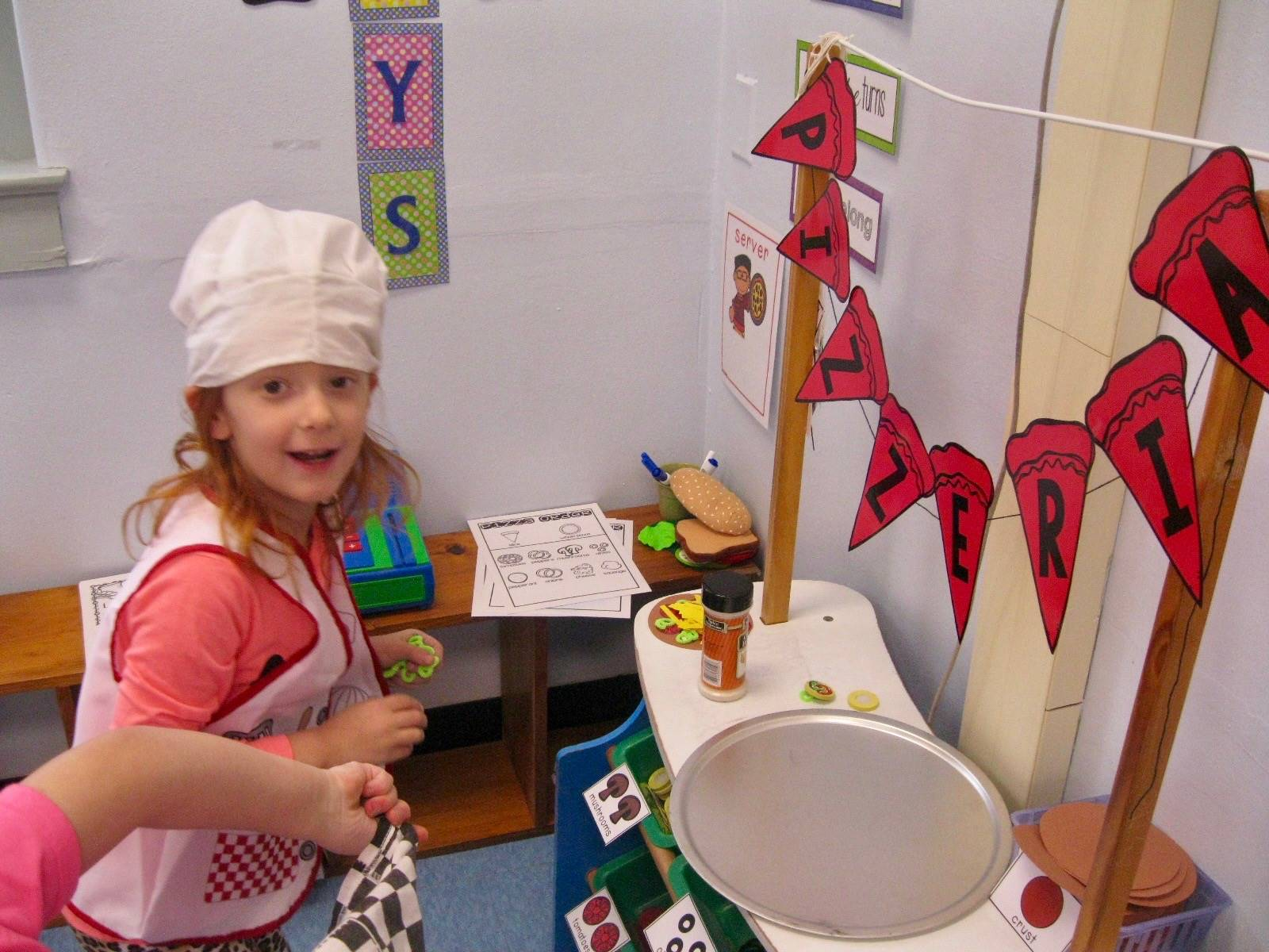 A child in chef hat plays pizzeria