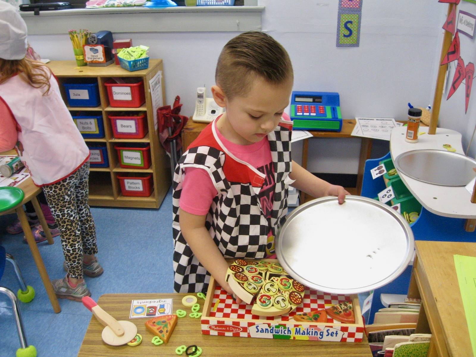 A student dishes pizza onto the pan.