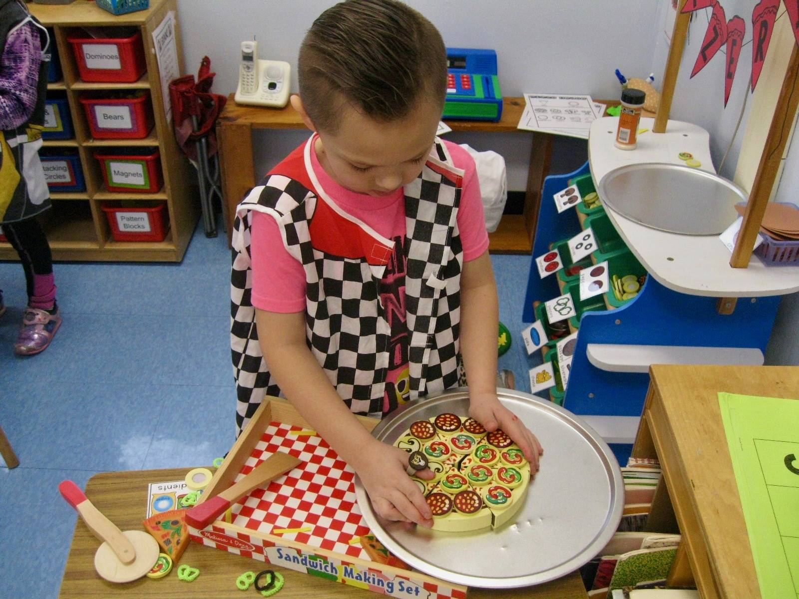 A student assembles pizza on to pan.