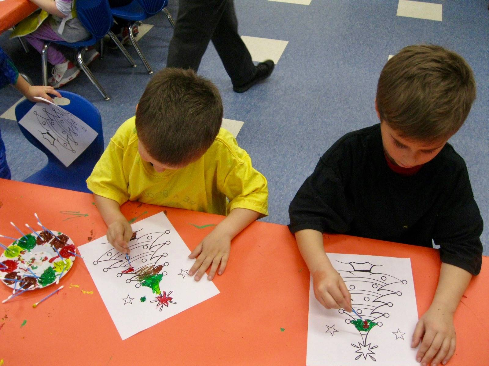 2 students add paint to  their paintings.