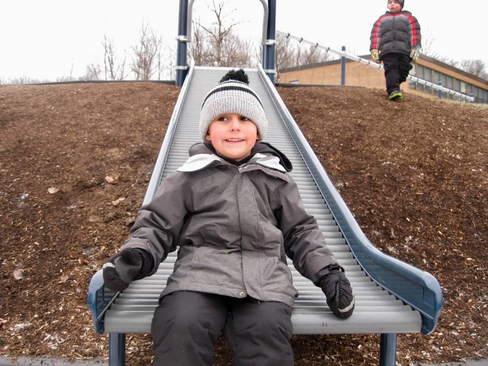 A student sits on roller slide.