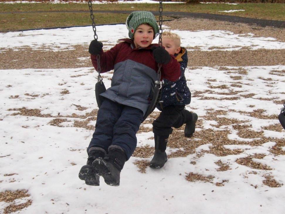 a student pushes another on swing.