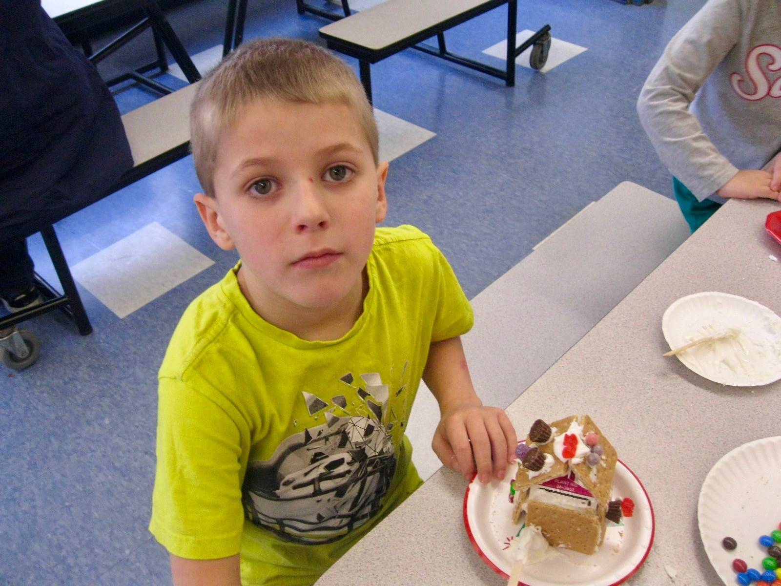 A student is proud of his gingerbread house.