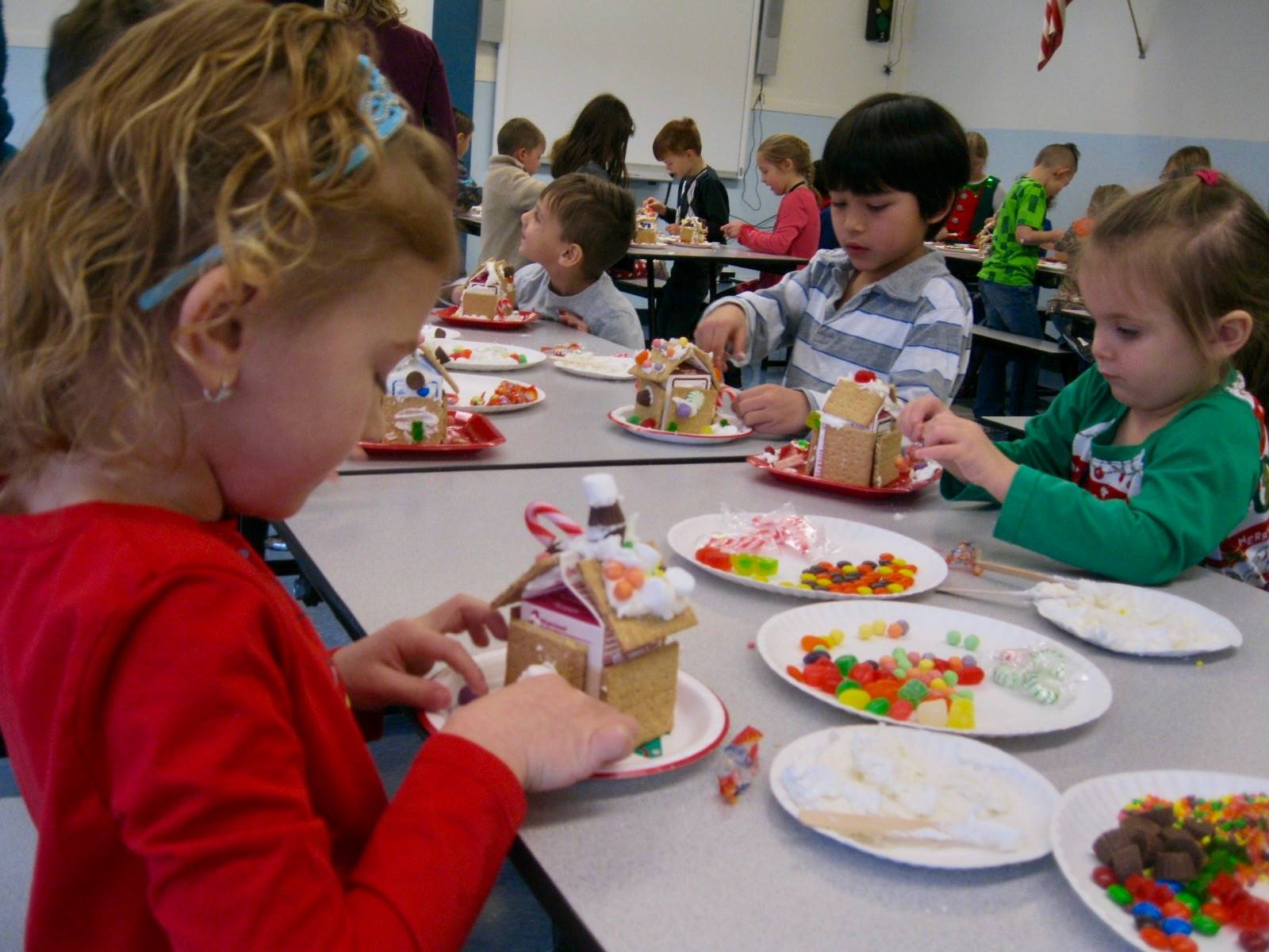 3 students show gingerbread houses.