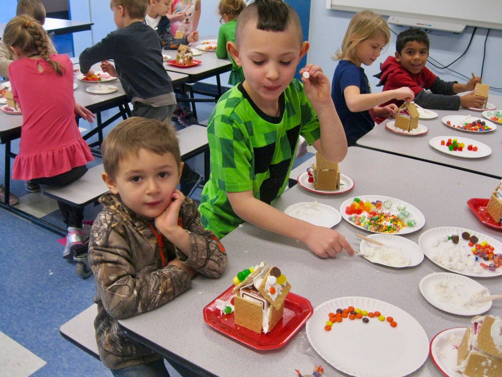 2 students show off gingerbread houses.